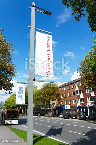Essen, Germany - August 7, 2011: View along street Bismarckstraße in Essen in summer. Alog sidewalk are banners and poles of museum. At left side a bus is parked. At right side are buildings.
