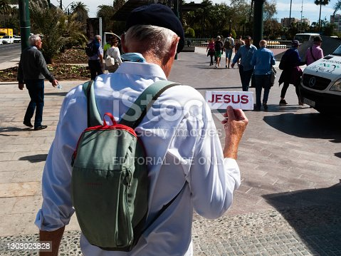 09.03.20. Malaga, Spain. Follow Jesus sign, old man with backpack. guidepost concept