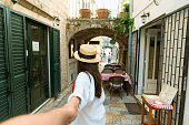 istock follow me concept. woman holding man hand in tight stone street of Budva 1131968164