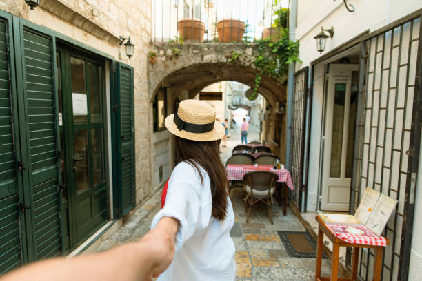 follow me concept. woman holding man hand in tight stone street of Budva stock photo
