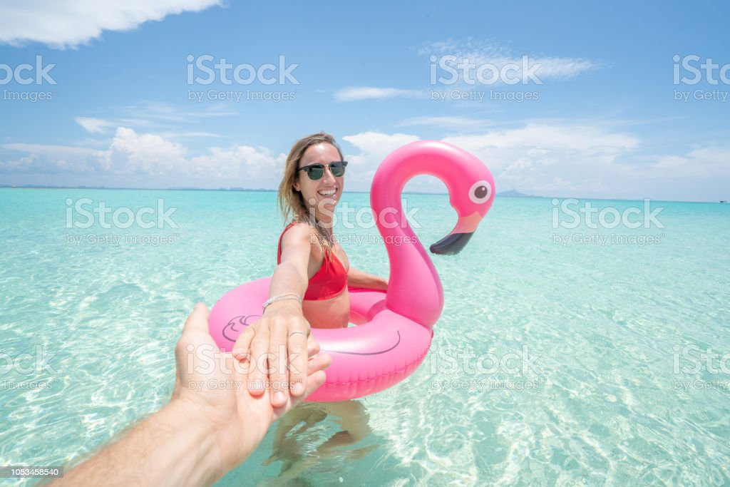 Folgen Sie mir Konzept Frau führenden Freund am Traumstrand mit aufblasbarer Flamingo spielen in unberührten klares Wasser in den Inseln von Thailand. Die Leute reisen Luxus Spaß und coole Haltung Konzept – Foto