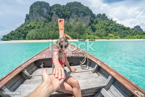 Follow me concept woman leading boyfriend on longtail Thai boat in pristine clear water in the Islands of Thailand. People travel destinations fun concept