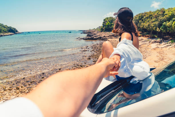 follow me concept woman sitting on the hood of the car resting at the beach stock photo