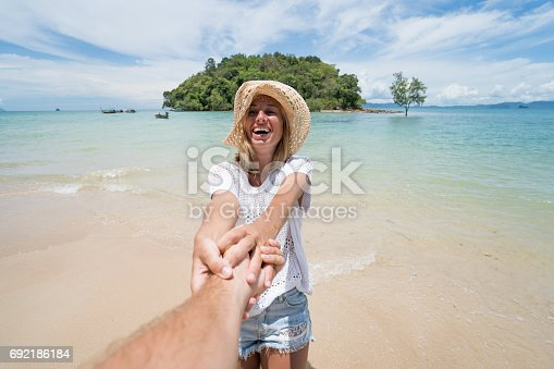 istock Follow me concept- Young woman leading man to tropical beach 692186184