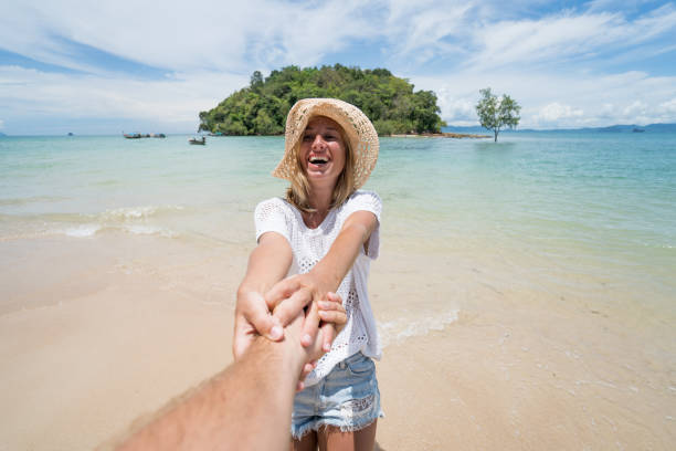 Follow me concept- Young woman leading man to tropical beach stock photo