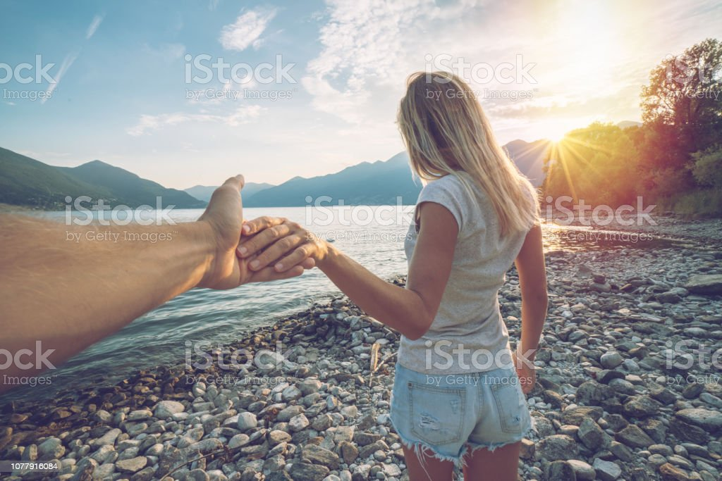 Follow me concept-Blond girlfriend leading man holding hand to...