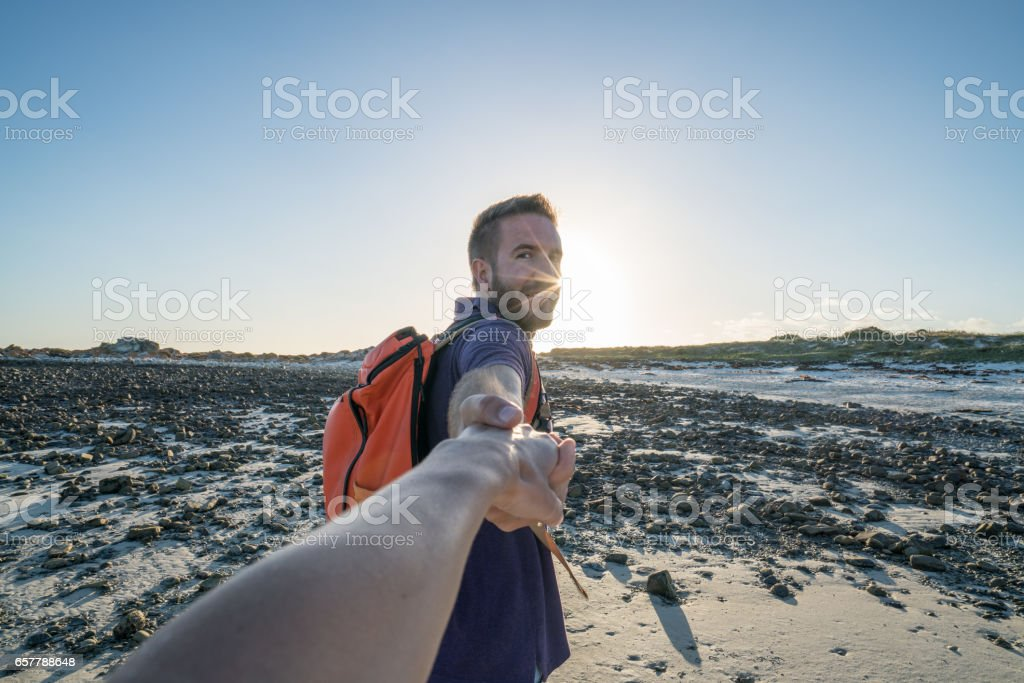 Follow me concept-Young man leading girlfriend to the beach stock photo