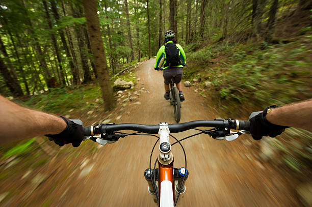 Follow me POV image of a mountain biker following another biker on a trail mountain biking stock pictures, royalty-free photos & images