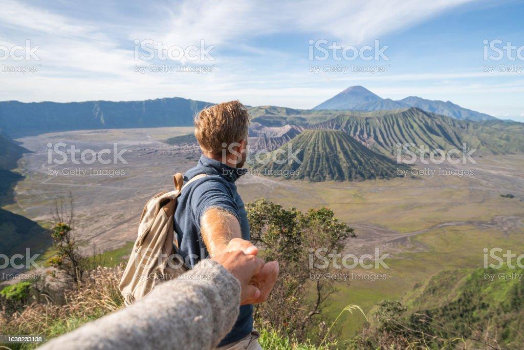 Follow me to concept, boyfriend leading person to volcanic landscape...
