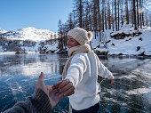 istock Follow me to concept; Happy young woman leading boyfriend to frozen lake at sunset 1201693745