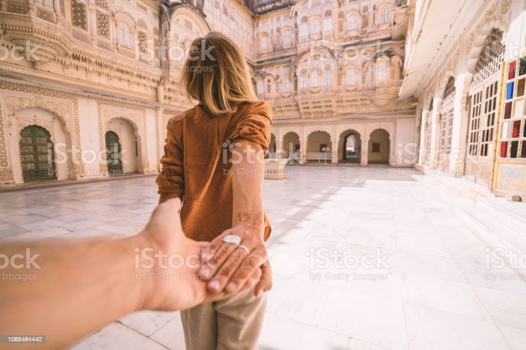 Follow me to concept; woman leading boyfriend holding hands inside...