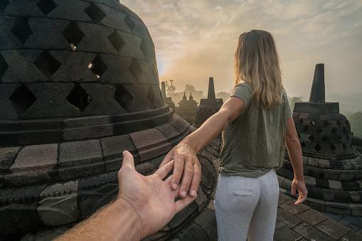 istock Follow me to concept, woman leading boyfriend to Borobudur temple at sunrise, Indonesia 924411838