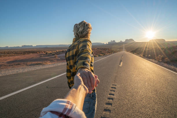 Follow me to concept; young man leading boyfriend to long highway road at sunset enjoying travel in the USA stock photo