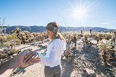 Follow me to concept; young woman leading boyfriend cactus garden, USA