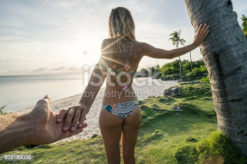 Follow me to concept young woman leading boyfriend to tropical beach at sunset, shot in Bantayan Island, Visayas Islands, Philippines. Idyllic tropical travel journey vacations concept.