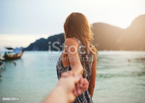 Shot of a young woman leading someone by the hand at the beach