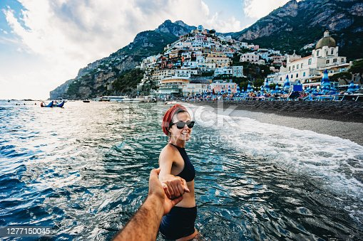Follow me to Positano, Italy - A young beautiful woman is leading her partner to the small town of Positano. She's bathing in the sea. Italy vacation concept like Dolce Vita.