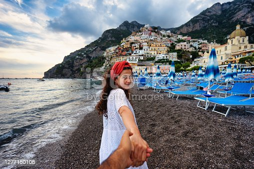 Follow me to Positano, Italy - A young beautiful woman is leading her partner to the small town of Positano. Italy vacation concept like Dolce Vita.