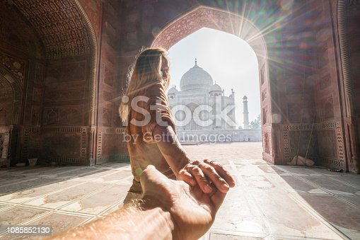 Follow me to the Taj Mahal, India. Female tourist leading boyfriend to there magnificent famous Mausoleum in Agra. People travel concept