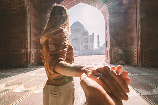 istock Follow me to the Taj Mahal, India. Female tourist leading boyfriend to there magnificent famous Mausoleum in Agra. People travel concept 1085852132