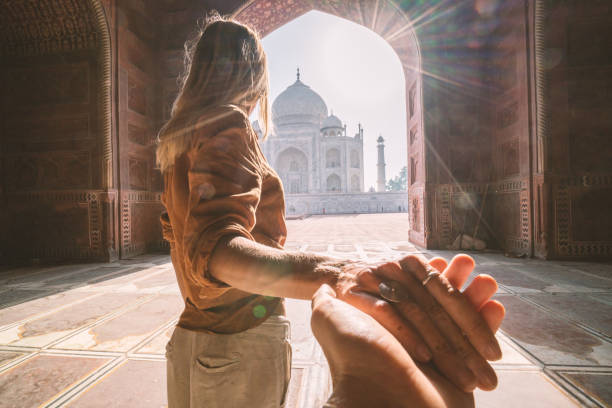 Follow me to the Taj Mahal, India. Female tourist leading boyfriend to there magnificent famous Mausoleum in Agra. People travel concept stock photo