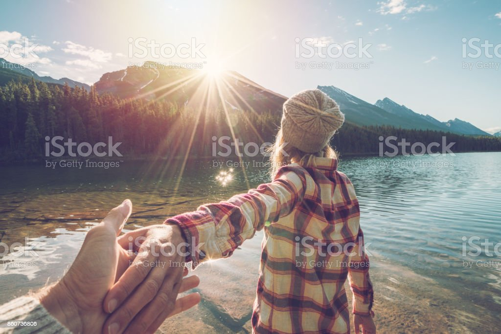 Follow me to- young woman leading man to mountain lake at sunrise stock photo