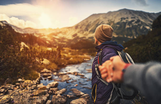 Follow me. Young woman showing the way during hiking activities stock photo