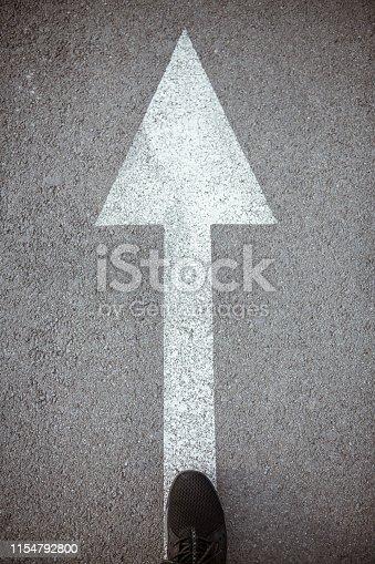 Man walking on white direction arrow