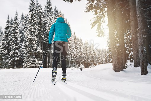 Beautiful young women cross-country skier gliding on the slope, pushing herself with ski poles. Wearing a winter suit to keep herself warm on this cold day in the outdoors.