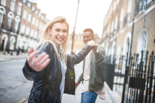 Follow us! A young couple enjoying each others company outdoors in London and inviting you to join them temptation stock pictures, royalty-free photos & images