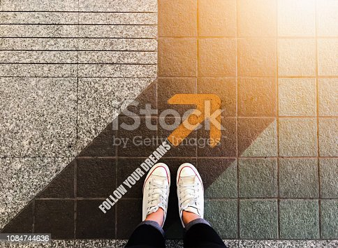 istock Follow your dreams yellow arrow and woman feet wear white sneakers shoe on floor background 1084744636