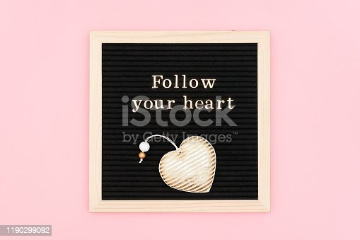 Follow your heart. Motivational quote in gold letters and decorative textile heart on black letter board on pink background. Top view Flat lay Concept inspirational quote of the day.