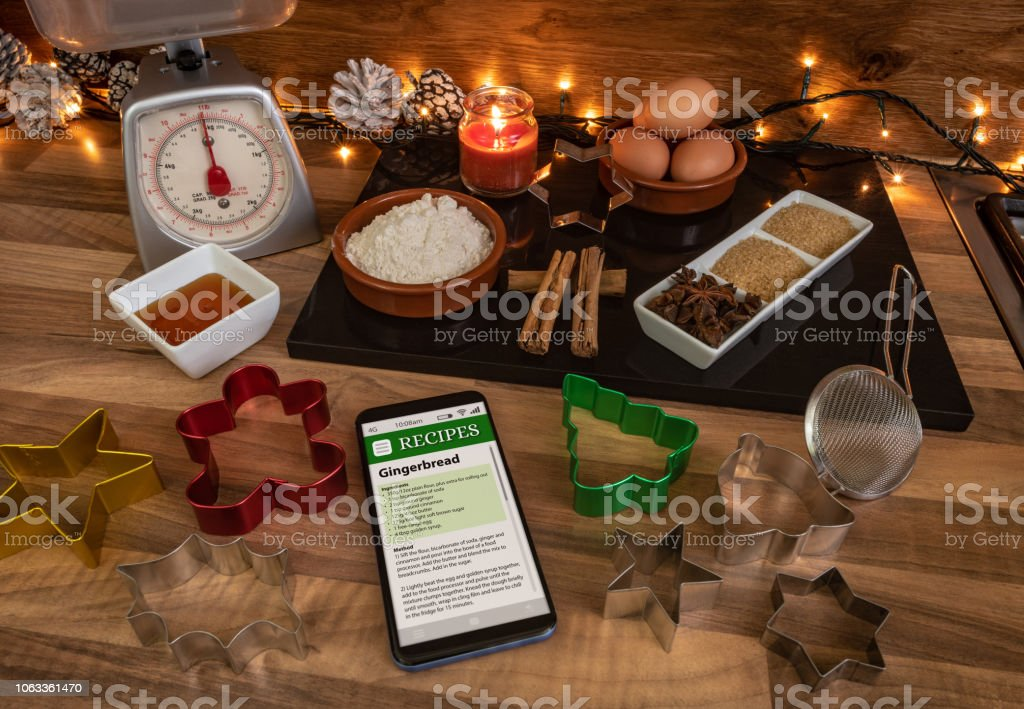 Following a recipe on a smartphone to make gingerbread stock photo