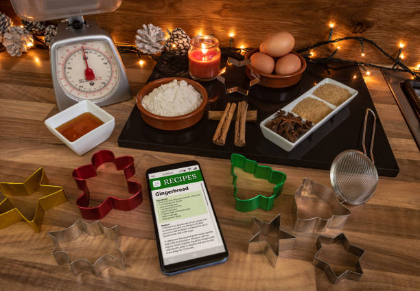 following a recipe on a smartphone to make gingerbread - christmas stock photos and pictures