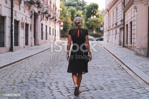 rear view mature adult woman in her forties in beautiful black cocktail dress walking alone through historical center city street with cobblestones on summer afternoon, shallow focus, background blurred