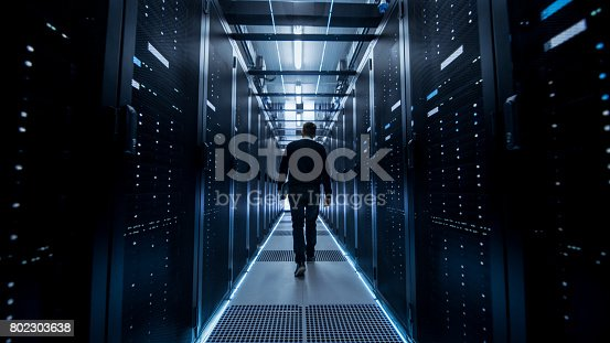899720520istockphoto Following Shot of IT Engineer Walking Through Data Center Corridor with Rows of Rack Servers. 802303638