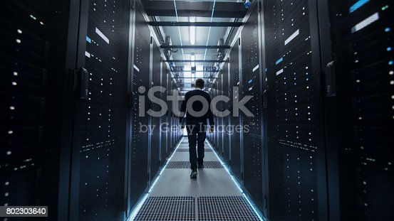 899720520istockphoto Following Shot of IT Engineer Walking Through Data Center Corridor with Rows of Rack Servers. 802303640