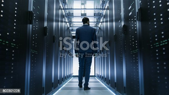 802303672istockphoto Following Shot of IT Engineer Walking Through Data Center with Rows of Working Rack Servers on Both Sides. 802301228