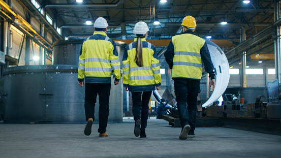 Following Shot Of Three Engineers Walking Through Heavy Industry Manufacturing Factory In The Background Welding Work In Progress Various Metalwork Pipeline Barrel Components Stock Photo - Download Image Now