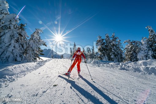rear view skiing woman female skier pushing along flat connection ski piste slope path on sunny winter vacation day in mountains with starshapped sun and trees along covered with deep snow