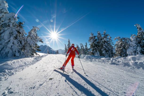 nach Skifahren Frau schieben entlang flacher Ski Piste auf sonnigen Wintertag – Foto