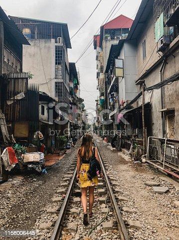 A rear-view shot of a young caucasian woman walking down a narrow railroad track.