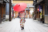 Japanese woman walking with traditonal umbrella in the traditional part of Kyoto.