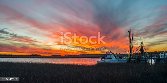 A fiery sky rises above moored fishing boats at Folly Beach, SC.