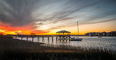 A dramatic sunset rises above residential boat docks at Folly Beach, SC.