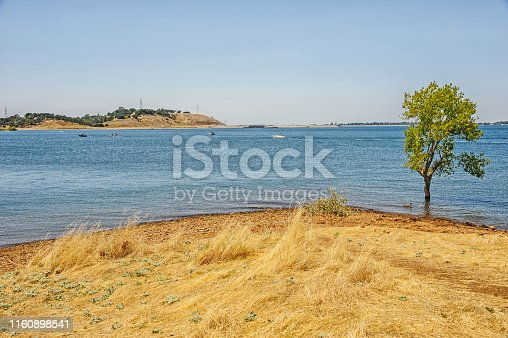 This view of Folsom Lake located near the Sacramento Metropolitan area it is multipurpose, the water can be used for generating hydro electric production as well as water for agriculture efforts and for the humans uses as well as recreation. The lake is now very full following the more than usual rains and snow falls. multiple locations are available for recreation and on this July day it looks beautiful.