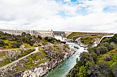 This panoramic view of the Hydroelectric Dam in Folsom California and the American River with four gates spilling water due to excessive inflow into Folsom Lake due to recent storms and snow in the Sierra Nevada Mountains under a beautiful cloudy sky.