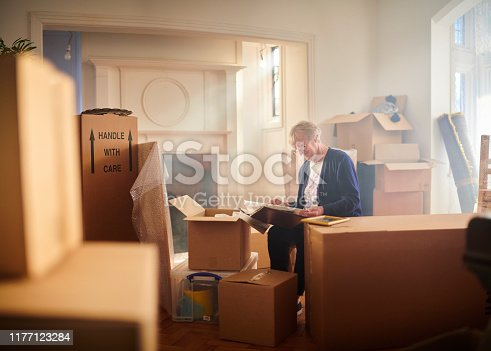 senior woman looks through some memories just before the house move begins