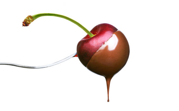 Fondue cherry in hot chocolate Fondue cherry in hot chocolate on a fork isolated on a white background chocolate fondue stock pictures, royalty-free photos & images