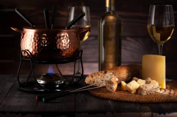 fondue mit käse und weißwein auf einem dunklen hintergrund aus holz - fondue zutaten stock-fotos und bilder